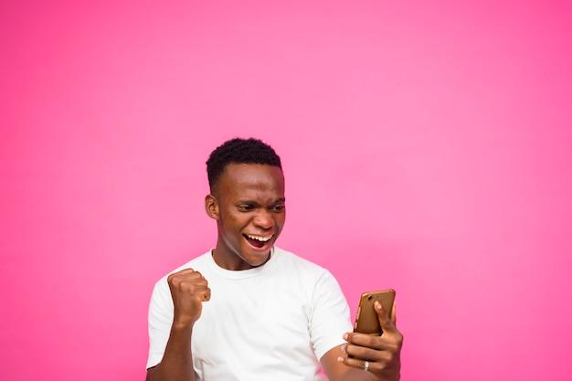Feliz como vencedor, jovem negro animado usando telefone inteligente isolado sobre fundo rosa