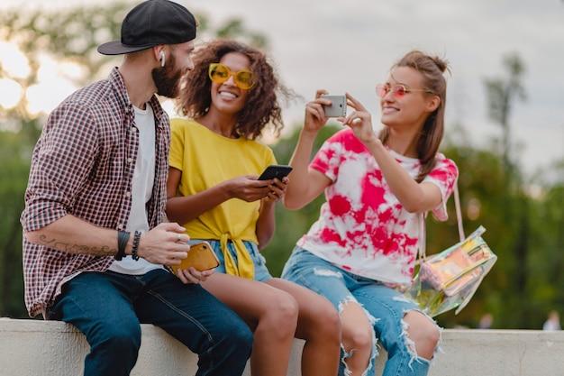 Feliz companhia jovem e elegante de amigos sentados no parque, homens e mulheres se divertindo juntos
