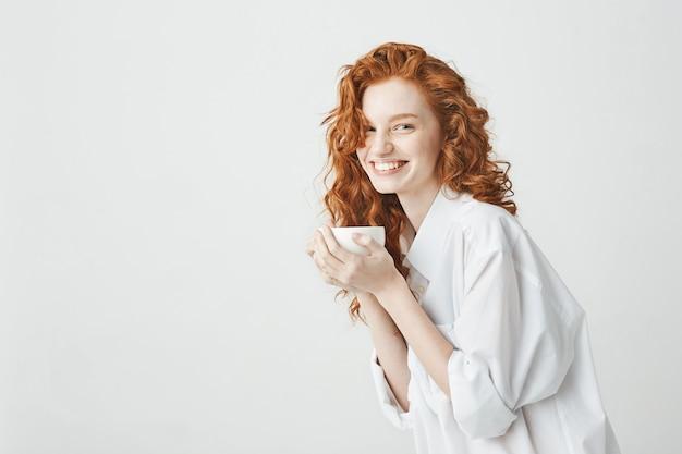 Feliz concurso garota ruiva na camisa sorrindo segurando copo sentado na mesa
