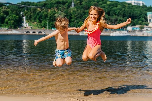 Feliz, crianças, pular, em, litoral