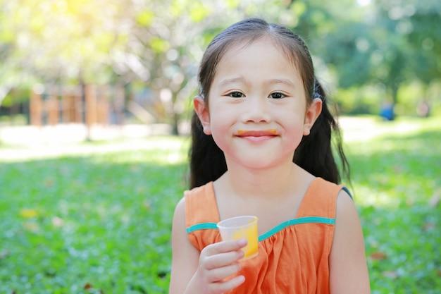 Feliz da menina que bebe o suco de laranja com manchado em torno de sua boca no jardim do verão.