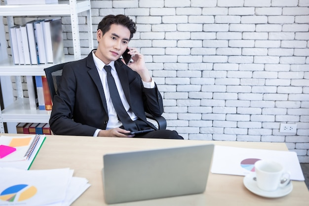 Feliz de asiático jovem empresário espera pegar smartphone trabalhando trabalhou com e laptop na mesa de madeira após perdas de negócios no fundo da sala de escritório.