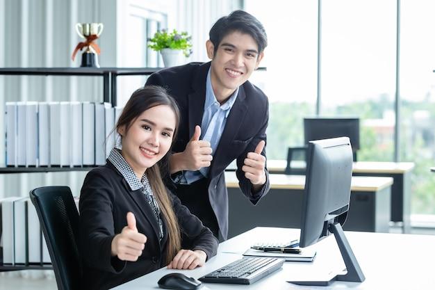 Feliz de parceiros de negócios e empresário mostrando polegares para cima discutindo negócios adultos positivos, trabalhando em conjunto com o computador na mesa de madeira e idéias na reunião no fundo do escritório.
