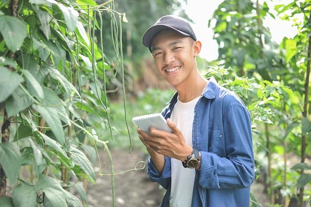 Feliz de sorrir jovem agricultor asiático segurando o caderno no jardim verde, no local.