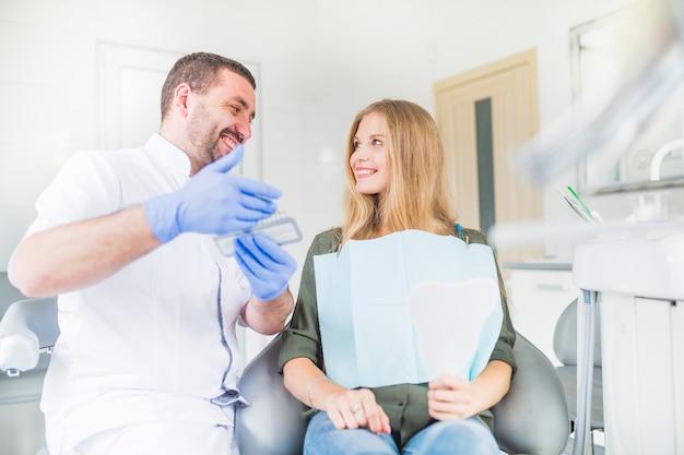 Feliz dentista e paciente olhando uns aos outros ao escolher o tom da cor de seus dentes