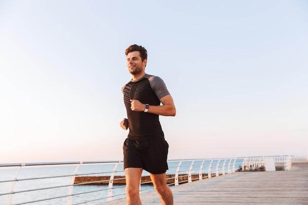 Feliz desportista de bermuda e camiseta correndo ao longo do cais ou calçadão à beira-mar, durante o nascer do sol