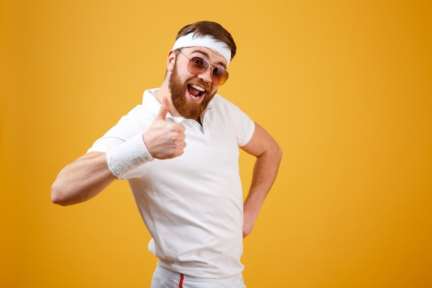 Feliz desportista em óculos de sol aparecendo polegar