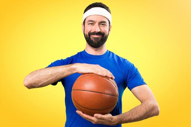 Feliz desportista engraçada com bola de basquete em fundo colorido