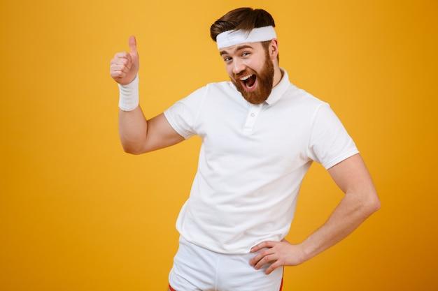 Feliz desportista mostrando o polegar para cima segurando o braço no quadril