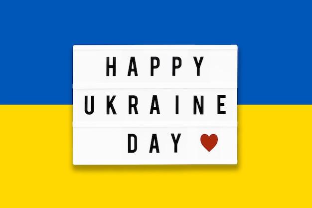 Feliz dia da ucrânia em uma mesa de luz em um fundo da cor da bandeira da ucrânia.