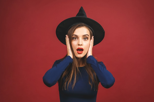 Feliz dia das bruxas bruxa com maquiagem brilhante e cabelos longos. mulher jovem e bonita surpresa posando em traje sexy de bruxas. isolado em fundo vermelho