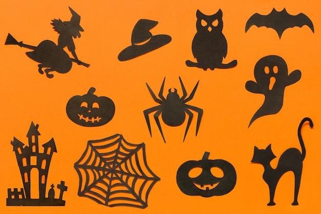 Feliz dia das bruxas conjunto silhuetas recortadas em papel preto sobre fundo laranja