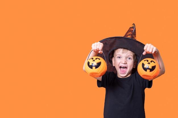 Feliz dia das bruxas. crianças assustadoras de halloween. menino assustador alegre segurando baldes de doces em forma de uma lanterna de abóbora para o halloween em fundo laranja, copie o espaço. conceito de doçura ou travessura.