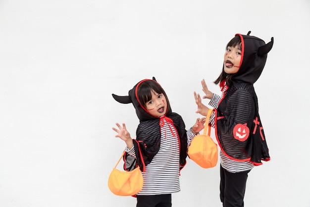 Feliz dia das bruxas! duas crianças em fantasias de halloween e com abóboras no fundo branco