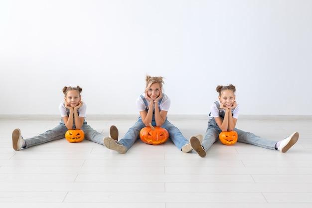 Feliz dia das bruxas e conceito de férias - uma mãe e suas filhas com abóboras. família feliz se preparando para o halloween.