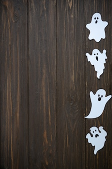 Feliz dia das bruxas feriado fundo com papel ofício em forma de fantasmas na mesa de madeira. celebração do feriado de halloween com decoração.