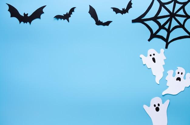 Feliz dia das bruxas feriado fundo com papel ofício em forma de fantasmas, teias de aranha e morcegos em azul. celebração do feriado de halloween com decoração.