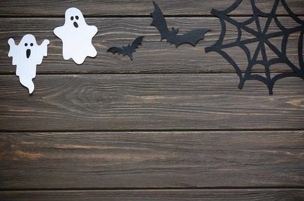 Feliz dia das bruxas feriado fundo com papel ofício em forma de fantasmas, teias de aranha e morcegos na mesa de madeira. celebração do feriado de halloween com decoração.
