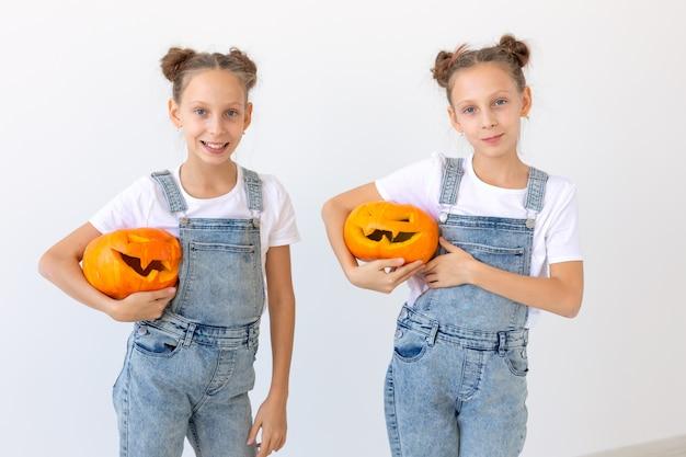Feliz dia das bruxas, feriados e conceito de infância - meninas gêmeas gêmeas com uma lanterna de abóboras se divertindo enquanto passam o tempo dentro de casa.