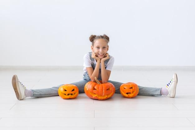 Feliz dia das bruxas, férias de outono e conceito de infância - menina bonitinha com uma abóbora jack-o'-lantern dentro de casa.