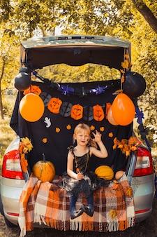 Feliz dia das bruxas fofa bruxinha com abóboras no porta-malas do carro