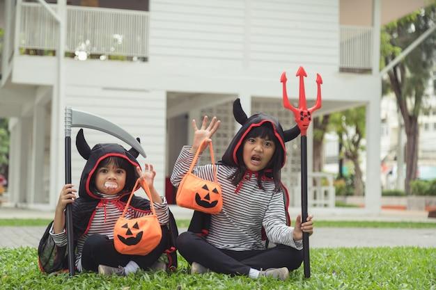 Feliz dia das bruxas. irmãzinha de terno e com abóboras em casa
