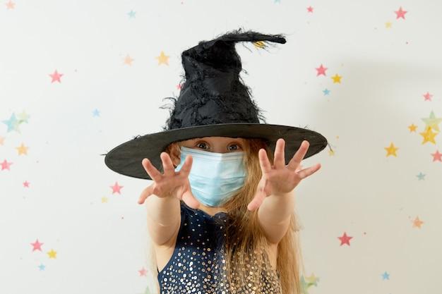 Feliz dia das bruxas . menina na fantasia de carnaval de bruxa e máscara de proteção facial.