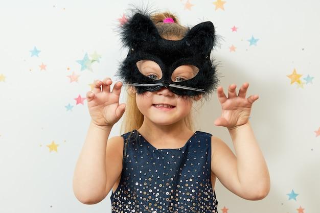 Feliz dia das bruxas . menina na máscara de gato preto, fantasia de carnaval. cara engraçada