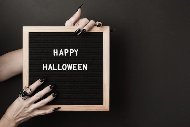Feliz dia das bruxas no quadro de cartas nas mãos com unhas pretas compridas e anel de aranha em fundo preto. conceito de férias de halloween.