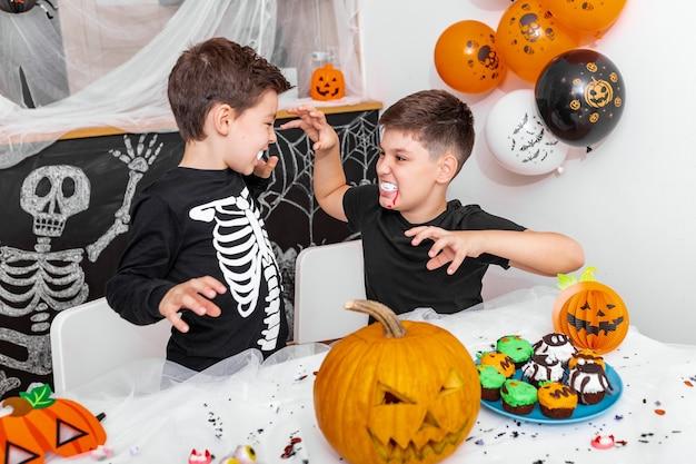 Feliz dia das bruxas! rapaz atraente com seu irmão mais velho estão se preparando para a festa de halloween. irmãos fantasiados estão se divertindo e assustando uns aos outros