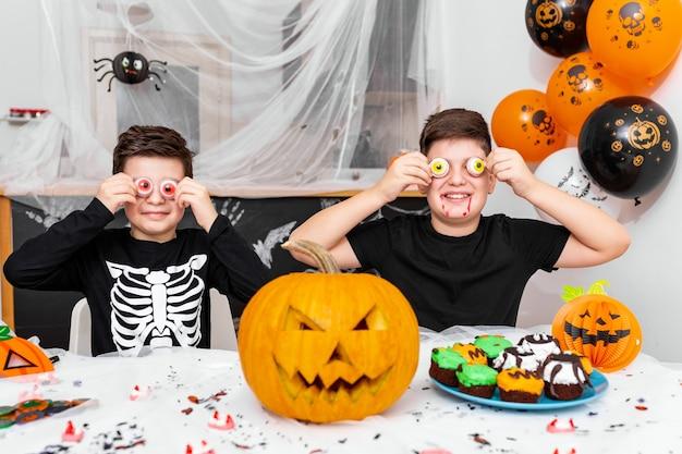 Feliz dia das bruxas! rapaz atraente com seu irmão mais velho estão se preparando para a festa de halloween. irmãos fantasiados estão se divertindo e brincando com a decoração de olhos assustadores