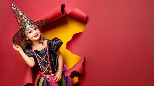 Feliz dia das bruxas. rindo engraçado criança garota em uma fantasia de bruxa de halloween olhando, sorrindo e assusta através de um buraco de fundo de papel vermelho e amarelo. copyspace