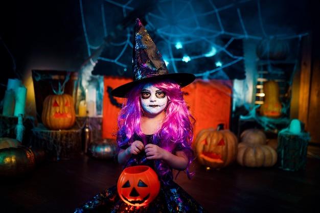 Feliz dia das bruxas. uma linda menina fantasiada de bruxa comemora em casa em um interior com abóboras e casa mágica de papelão ao fundo
