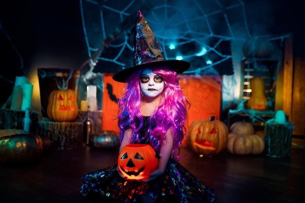 Feliz dia das bruxas. uma linda menina fantasiada de bruxa comemora em casa em um interior com abóboras e casa mágica de papelão
