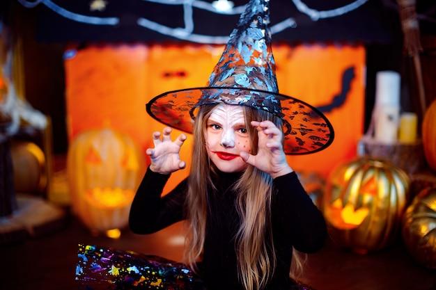 Feliz dia das bruxas. uma menina linda em uma fantasia de bruxa comemora com abóboras