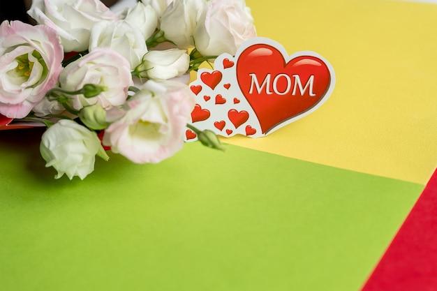 Feliz dia das mães. buquê de flores brancas eustoma com coração vermelho em fundo brilhante. flores de primavera para o dia das mães.