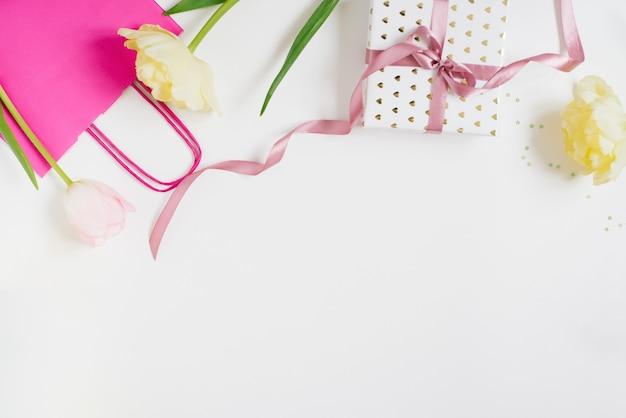 Feliz dia das mães, dia da mulher ou conceito de saudação do dia dos namorados. fundo de cores pastel com flores tulipa e caixa de presente, plana leigos com espaço de cópia.