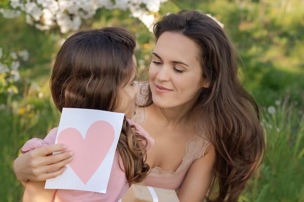 Feliz dia das mães! filha criança dá mãe um cartão de coração e um presente.