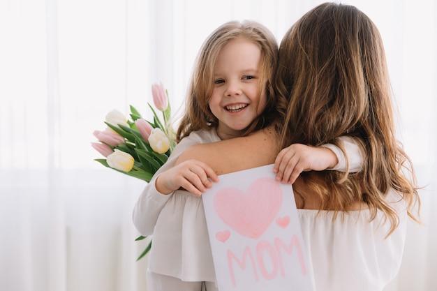 Feliz dia das mães. filha criança felicita mães e dá-lhe um cartão postal e flores tulipas.