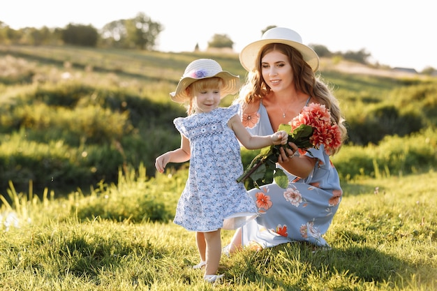 Feliz dia das mães. filha infantil parabeniza a mãe e lhe dá um buquê de flores ao ar livre.