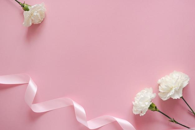 Feliz dia das mães. flor branca com fita em um fundo rosa pastel com vista superior do copyspace