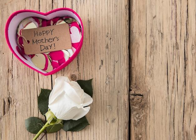 Feliz dia das mães inscrição com rosa na mesa