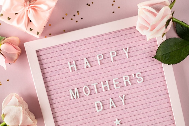 Feliz dia das mães palavras no quadro de cartas de feltro rosa. composição festiva com rosas e uma caixa com um presente numa superfície rosa. vista superior, configuração plana. copie o espaço.