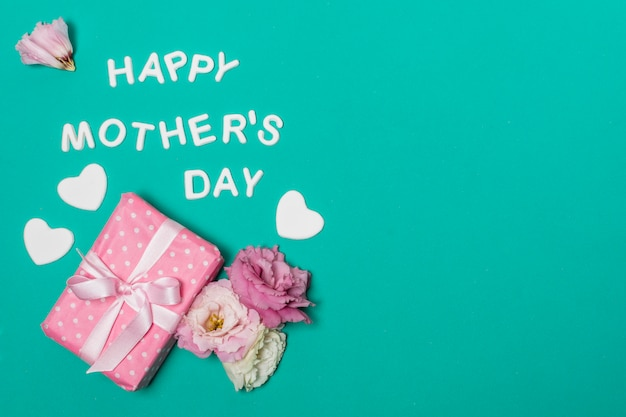 Feliz dia das mães título perto de flores e caixa de presente