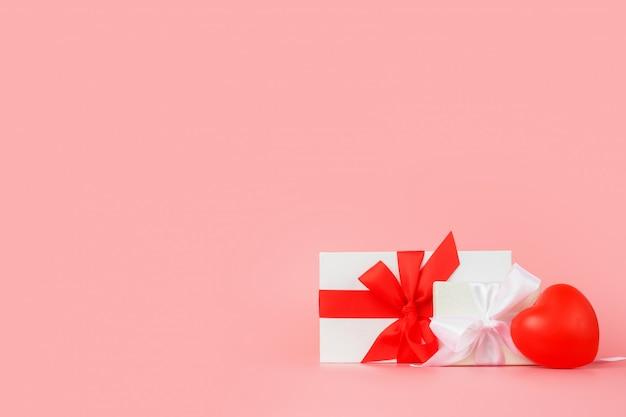 Feliz dia das mulheres modelo de design. caixa de presente branca decorativa com laço vermelho sobre fundo rosa pastel.