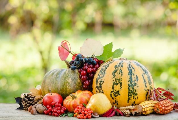 Feliz dia de ação de graças ainda vida. frutas, nozes e vegetais, colheita de outono na mesa ao ar livre