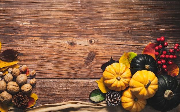 Feliz dia de ação de graças com abóbora e nozes na mesa de madeira