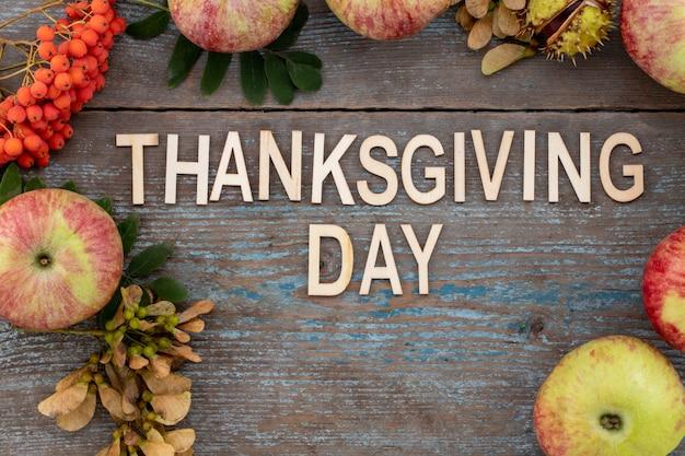 Feliz dia de ação de graças - texto com fundo de outono de folhas caídas e frutos com ajuste de lugar vintage na velha mesa de madeira.