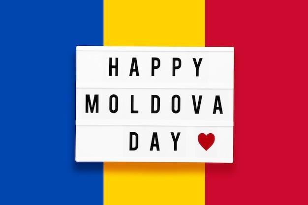 Feliz dia de moldova em uma mesa de luz em um fundo da cor da bandeira da moldávia.