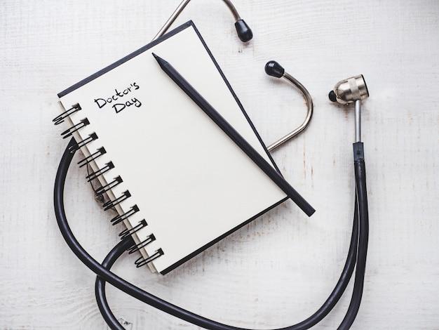 Feliz dia do médico. lindo cartão. caderno com inscrição de congratulações